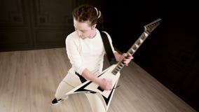 Μοντέρνος σόλο κιθαρίστας με τα dreadlocks στο κεφάλι του και στα άσπρα ενδύματα σε ένα μαύρο παιχνίδι υποβάθρου εκφραστικά απόθεμα βίντεο