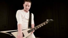 Μοντέρνος σόλο κιθαρίστας με τα dreadlocks στο κεφάλι του και στα άσπρα ενδύματα σε ένα μαύρο παιχνίδι υποβάθρου εκφραστικά φιλμ μικρού μήκους