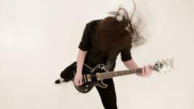 Μοντέρνος σόλο κιθαρίστας με τα dreadlocks στο κεφάλι του και στα μαύρα ενδύματα σε ένα άσπρο παιχνίδι υποβάθρου εκφραστικά φιλμ μικρού μήκους