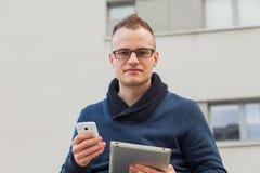 Μοντέρνος τύπος που συνδέονται στο διαδίκτυο με την ταμπλέτα και κινητό τηλέφωνο στην πόλη Είναι ευτυχής Στοκ φωτογραφίες με δικαίωμα ελεύθερης χρήσης