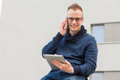 Μοντέρνος τύπος που συνδέονται στο διαδίκτυο με την ταμπλέτα και κινητό τηλέφωνο στην πόλη Είναι ευτυχής Στοκ Εικόνες