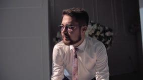 Μοντέρνος τύπος στα γυαλιά και άσπρη συνεδρίαση πουκάμισων σε μια καρέκλα σε ένα όμορφο δωμάτιο απόθεμα βίντεο
