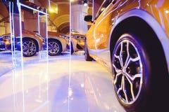 Μοντέρνος φωτεινός αυτόματος παρουσιάζει διάφορα νέα αυτοκίνητα που σταθμεύουν στην αποθήκη εμπορευμάτων εμπόρων ` αυτοκινήτων, σ Στοκ Φωτογραφίες