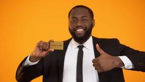 Μοντέρνος χαμογελώντας μαύρος στη formalwear παρουσιάζοντας χρυσή κάρτα και αντίχειρας-επάνω απόθεμα βίντεο