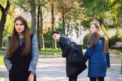 Μοντέρνο άπιστο νέο αρσενικό άσχημο να κοιτάξει επίμονα στο μοντέρνο κορίτσι και καθιστά ζηλότυπη τη φίλη του που περπάτησε ακριβ Στοκ εικόνες με δικαίωμα ελεύθερης χρήσης