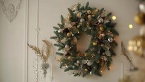 Μοντέρνο άσπρο εσωτερικό με τα χριστουγεννιάτικα δέντρα έλατου, και σύνολο στεφανιών των χρυσών διακοσμήσεων, των παιχνιδιών, των φιλμ μικρού μήκους