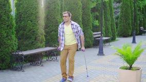 Μοντέρνο άτομο με έναν τραυματισμό στα δεκανίκια που περπατούν στο πάρκο μια ηλιόλουστη ημέρα φιλμ μικρού μήκους