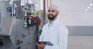 Μοντέρνο άτομο μηχανικών με μια γενειάδα ειδικό άσπρο σε έναν ομοιόμορφο ελεγκτικός τη βιομηχανική μηχανή φιλμ μικρού μήκους