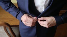 Μοντέρνο άτομο που κουμπώνει ένα σακάκι που προετοιμάζεται για την έξοδο o απόθεμα βίντεο