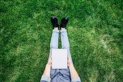Μοντέρνο άτομο που χρησιμοποιεί την ψηφιακή ταμπλέτα με την κενή οθόνη καθμένος στην πράσινη χλόη Στοκ φωτογραφία με δικαίωμα ελεύθερης χρήσης