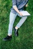 Μοντέρνο άτομο που χρησιμοποιεί την ψηφιακή ταμπλέτα με την κενή οθόνη καθμένος στην πράσινη χλόη Στοκ Εικόνα