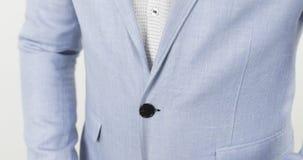 Μοντέρνο άτομο σε ένα μπλε κοστούμι που στερεώνει το μαύρο κουμπί στο σακάκι του που προετοιμάζεται στο κόμμα απόθεμα βίντεο