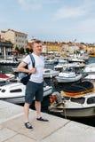 Μοντέρνο άτομο τουριστών Α σε μια άσπρη μπλούζα και τα σορτς που στέκονται στο ανάχωμα μιας ευρωπαϊκής πόλης με ένα σακίδιο πλάτη Στοκ φωτογραφία με δικαίωμα ελεύθερης χρήσης
