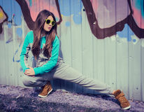 Μοντέρνο έφηβη στα ζωηρόχρωμα γυαλιά ηλίου που θέτουν κοντά στα γκράφιτι στοκ φωτογραφία