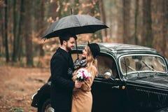 Μοντέρνο αγαπώντας γαμήλιο ζεύγος που φιλά και που αγκαλιάζει σε ένα δάσος πεύκων κοντά στο αναδρομικό αυτοκίνητο Στοκ Εικόνα