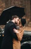 Μοντέρνο αγαπώντας γαμήλιο ζεύγος που φιλά και που αγκαλιάζει σε ένα δάσος πεύκων κοντά στο αναδρομικό αυτοκίνητο Στοκ εικόνες με δικαίωμα ελεύθερης χρήσης