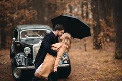 Μοντέρνο αγαπώντας γαμήλιο ζεύγος που φιλά και που αγκαλιάζει σε ένα δάσος πεύκων κοντά στο αναδρομικό αυτοκίνητο Στοκ Φωτογραφία