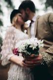 Μοντέρνο αγαπώντας γαμήλιο ζεύγος που φιλά και που αγκαλιάζει σε ένα δάσος πεύκων κοντά στο αναδρομικό αυτοκίνητο Στοκ φωτογραφίες με δικαίωμα ελεύθερης χρήσης