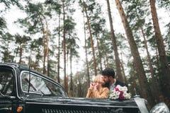 Μοντέρνο αγαπώντας γαμήλιο ζεύγος που φιλά και που αγκαλιάζει σε ένα δάσος πεύκων κοντά στο αναδρομικό αυτοκίνητο Στοκ εικόνα με δικαίωμα ελεύθερης χρήσης