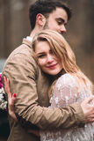 Μοντέρνο αγαπώντας γαμήλιο ζεύγος που φιλά και που αγκαλιάζει σε ένα δάσος πεύκων κοντά στο αναδρομικό αυτοκίνητο Στοκ Εικόνες