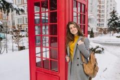 Μοντέρνο βρετανικό πορτρέτο της γοητείας της νέας γυναίκας με τη μακριά τρίχα brunette που περπατά στην οδό κοντά στο κόκκινο τηλ στοκ φωτογραφία