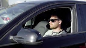 Μοντέρνο επιτυχές άτομο που οδηγεί ένα μαύρο αυτοκίνητο πολυτέλειας το καλοκαίρι απόθεμα βίντεο