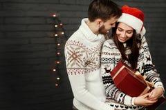 Μοντέρνο ευτυχές ζεύγος με το μεγάλο κόκκινο παρόν χαμογελώντας ήπια να αγκαλιάσει Στοκ εικόνα με δικαίωμα ελεύθερης χρήσης