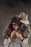 Μοντέρνο ζεύγος hipster που αγκαλιάζει ήπια άτομο στο αισθησιακό touchi καπέλων στοκ φωτογραφίες