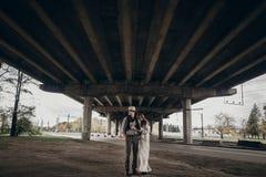 Μοντέρνο ζεύγος hipster που θέτει την κάτω εγκαταλειμμένη γέφυρα τσιγγάνος boho Στοκ εικόνα με δικαίωμα ελεύθερης χρήσης