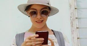 Μοντέρνο θηλυκό smartphone χρησιμοποίησης κοντά στο shabby κτήριο απόθεμα βίντεο