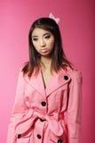 Μοντέρνο ιαπωνικό κορίτσι σε ρόδινο Outwear πέρα από το χρωματισμένο υπόβαθρο Στοκ Φωτογραφίες