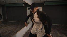 Μοντέρνο και όμορφο κορίτσι που χορεύει ένας σύγχρονος χορός κοντά στον καθρέφτη στην αίθουσα χορού Σπουδαστής μετά από το τέλος  απόθεμα βίντεο