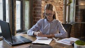 Μοντέρνο καυκάσιο κορίτσι σχεδιαστών που χρησιμοποιεί μια συνεδρίαση lap-top σε έναν πίνακα στο καθιερώνον τη μόδα τούβλινο εσωτε φιλμ μικρού μήκους