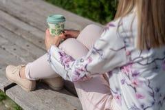 Μοντέρνο κορίτσι με ένα φλιτζάνι του καφέ στα πόδια που κάθονται σε έναν πάγκο σε ένα πάρκο στοκ εικόνες με δικαίωμα ελεύθερης χρήσης