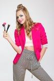 Μοντέρνο κορίτσι με τη μακριά σγουρή τρίχα βούρτσες μιας στις ρόδινες σακακιών κοριτσιών εκμετάλλευσης για τη σύνθεση Στοκ Εικόνες