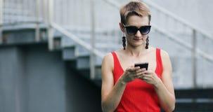 Μοντέρνο κορίτσι με το σύντομο μήνυμα γραψίματος hairstyle που χρησιμοποιεί το έξυπνο τηλέφωνο απόθεμα βίντεο