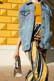 Μοντέρνο κορίτσι σε ένα σακάκι τζιν, κίτρινη κορυφή και σε μια φούστα με μια διακόσμηση σε μια βιασύνη, που κυματίζει μια άσπρη τ στοκ εικόνες με δικαίωμα ελεύθερης χρήσης
