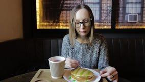 Μοντέρνο κορίτσι στα γυαλιά με ένα χαμόγελο που τρώει pankcakes με το σιρόπι και συνεδρίαση τσαγιού κατανάλωσης τη βοτανική σε έν απόθεμα βίντεο