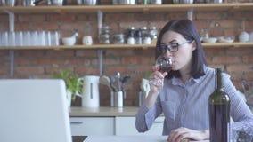 Μοντέρνο κορίτσι στα ποτά γυαλιών από ένα ποτήρι του κρασιού στην κουζίνα στο σπίτι στοκ εικόνα με δικαίωμα ελεύθερης χρήσης