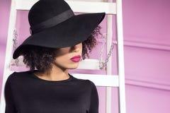 Μοντέρνο κορίτσι στην τοποθέτηση μαύρων καπέλων Στοκ φωτογραφία με δικαίωμα ελεύθερης χρήσης