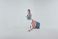 Μοντέρνο κορίτσι hipster στην αμερικανική πατριωτική εξάρτηση που κρατά μεγάλη εμείς τη σημαία που απομονωνόμαστε στο γκρι Στοκ φωτογραφία με δικαίωμα ελεύθερης χρήσης