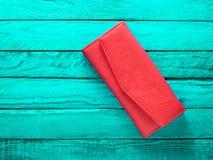 Μοντέρνο κόκκινο πορτοφόλι σε ένα τυρκουάζ ξύλινο υπόβαθρο Τοπ όψη Στοκ Εικόνες