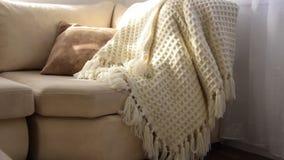 Μοντέρνο λαμπρά εσωτερικό του καθιστικού Άνετος καναπές πρόσκλησης με το χειροποίητο μάλλινο κάλυμμα απόθεμα βίντεο