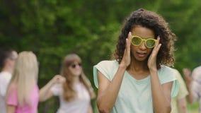 Μοντέρνο μικτό κορίτσι φυλών που χορεύει στο φεστιβάλ μουσικής, φίλοι που κρεμά έξω στο πάρκο απόθεμα βίντεο