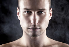 Μοντέρνο νέο αξύριστο άτομο με τα γκρίζος-μπλε μάτια γκρίζο σε έναν καπνώή Στοκ Εικόνες