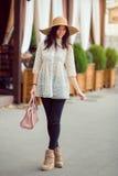 Μοντέρνο νέο ασιατικό κορίτσι που περπατά στην οδό πόλεων ενάντια στην πρόσοψη καφέδων Στοκ Φωτογραφία