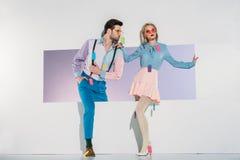 μοντέρνο νέο ζεύγος με τις ζωηρόχρωμες ετικέττες στα ενδύματα που περπατά μέσω του ανοίγματος Στοκ εικόνα με δικαίωμα ελεύθερης χρήσης