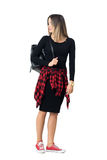 Μοντέρνο νέο περιστασιακό κορίτσι στη μαύρη φέρνοντας τσάντα φορεμάτων που κοιτάζει πίσω από πέρα από τον ώμο Στοκ Εικόνα