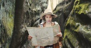 Μοντέρνο νέο ταξιδιωτικό κορίτσι στο καπέλο που εξετάζει το χάρτη, που εξερευνά τα ξύλα απόθεμα βίντεο