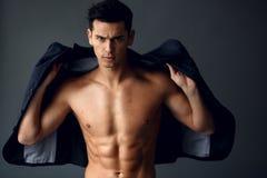 Μοντέρνο νέο όμορφο άτομο που στέκεται και που θέτει στο μοντέρνο κοστούμι σε έναν γυμνό κορμό, που απομονώνεται στο γκρίζο υπόβα στοκ φωτογραφία